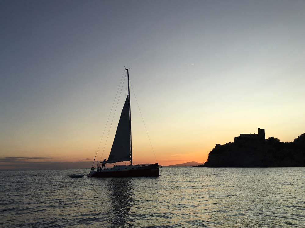 Barca a vela al tramonto nelle acque della Maremma